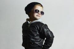 Modna dziecko chłopiec w okularach przeciwsłonecznych Zima styl chłopak trochę się uśmiecha Zdjęcia Royalty Free