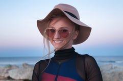 Modna dziewczyna jest relaksująca na plaży przy zmierzchem Zdjęcia Royalty Free