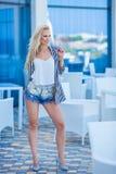 Modna fotografia wspaniała młoda dama z blond kędzierzawym włosy i jaskrawym makeup w eleganckiej nowożytnej sukni cajgi i cukier obrazy stock