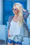 Modna fotografia wspaniała młoda dama z blond kędzierzawym włosy i jaskrawym makeup w eleganckiej nowożytnej sukni cajgi i cukier obrazy royalty free