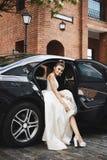 Modna i seksowna długa iść na piechotę brunetka modela dziewczyna z jaskrawym makeup w modnej srebro sukni siedzi w luksusowym sa obrazy stock