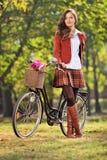 Modna kobieta pozuje z jej bicyklem w parku Obraz Royalty Free