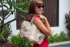 Modna kobieta w czerwieni sukni mienia snakeskin pytonu rzemiennej torbie Elegancki strój Zamyka up kiesa w rękach Zdjęcia Royalty Free