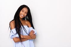Modna młoda afrykańska kobieta z galonową fryzury pozycją z rękami krzyżuje przeciw białemu tłu zdjęcie royalty free