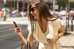 Modna młoda brunetka śmia się w telefon Zdjęcie Stock