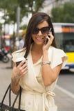 Modna młoda brunetka śmia się w telefon Obraz Royalty Free