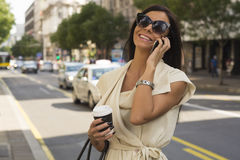 Modna młoda brunetka śmia się w telefon Obrazy Royalty Free