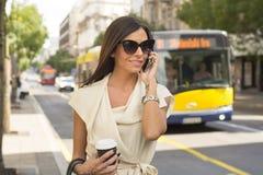 Modna młoda brunetka śmia się w telefon Fotografia Royalty Free