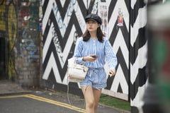 Modna młoda dziewczyna w błękitnych pasiastych kombinezonach i czarnej nakrętce iść puszek ulica w wschodnim Londyn Obraz Royalty Free