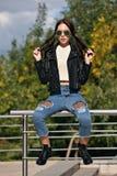 Modna młoda kobieta w skała stylu odziewa, czarna skórzana kurtka, niebiescy dżinsy, rajstopy w siatce pod powyginanymi cajgami Zdjęcia Royalty Free