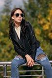 Modna młoda kobieta w skała stylu odziewa, czarna skórzana kurtka, niebiescy dżinsy, rajstopy w siatce pod powyginanymi cajgami Zdjęcie Stock