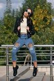 Modna młoda kobieta w skała stylu odziewa, czarna skórzana kurtka, niebiescy dżinsy, rajstopy w siatce pod powyginanymi cajgami Fotografia Royalty Free