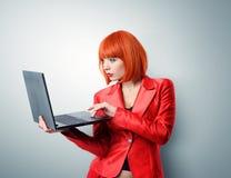 Modna młoda rudzielec kobieta trzyma laptop w czerwieni obrazy stock