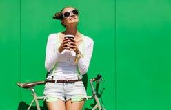Modna piękna młoda Ładna dziewczyna w zielenieć ścianę, chłodno okularów przeciwsłonecznych stojaki z rowerowym dylemat przekładn Fotografia Stock