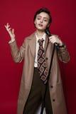 Modna piękna piosenkarz dziewczyna w retro żakiecie, krawacie i spodniach z mikrofonem w rękach pozuje na czerwonym tle, zdjęcia royalty free