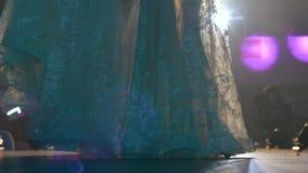 Modne kolorowe długie suknie na modelach na pokazie mody w świetle lamp, nogi tylko zbiory