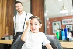 Modnej chłopiec Wzruszający włosy Po ostrzyżenia W fryzjera męskiego sklepie zdjęcie royalty free