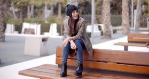 Modnej młodej kobiety siedzący czekanie na ławce zdjęcie royalty free