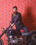 Modniś, brutalny rowerzysta na poważnej twarzy w skórzanej kurtce dostaje na motocyklu Mężczyzna z brodą, rowerzysta w skórzanej  obrazy stock