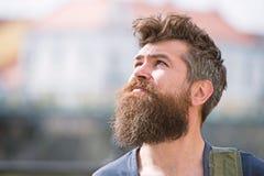 Modniś z brodą i wąsy na surowych twarzy spojrzeniach przy niebem, miastowy tło, defocused Brodaty facet cieszy się pogodnego zdjęcia stock