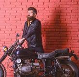 Modniś, brutalny rowerzysta na poważnej twarzy w skórzanej kurtce dostaje na motocyklu Początek podróży pojęcie brody ludzi zdjęcie stock