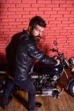 Modniś, brutalny rowerzysta na surowej twarzy w skórzanej kurtce siedzi puszek na motocyklu Mężczyzna z brodą, rowerzysta w skórz fotografia royalty free