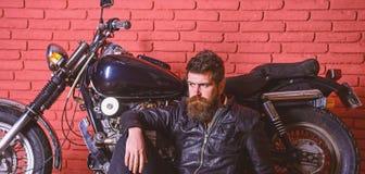 Modniś, brutalny rowerzysta na zadumanej twarzy w skórzanej kurtce siedzi na podłogowym pobliskim motocyklu Brutalny rowerzysty p obraz stock