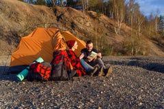 Modniś caucasian pary rekonesansowa mapa w górze podczas słonecznego dnia podczas gdy siedzą w namiocie fotografia stock