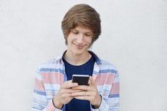 Modniś chłopiec trzyma mądrze telefonu pisać na maszynie wiadomości jego dziewczyna zadawala wyrażenie mówi ona o jego miłości Ro zdjęcia stock