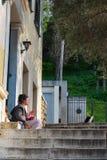 Modniś dziewczyna bawić się bęben sadzającego na krokach dom w Plaka Ateny blisko kota w pobliżu obrazy royalty free