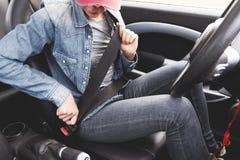 Modniś dziewczyna jest ubranym cajgów ubrania przymocowywa jej pas bezpieczeństwa w samochodzie obrazy royalty free