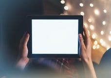 Modniś dziewczyna używa pastylki technologię w domowej atmosferze, osoby mienia komputer na tło łuny bokeh bożych narodzeń illimi obraz stock