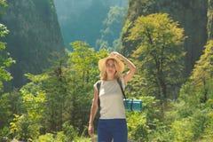 Modniś dziewczyna w kapeluszu podróżuje w górach dziewczyna kocha podróżować Widok od plecy turystyczny podróżnik dalej obrazy royalty free
