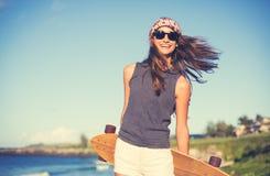 Modniś dziewczyna z łyżwa deskowymi jest ubranym okularami przeciwsłonecznymi obraz royalty free