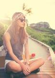 Modniś dziewczyna z łyżwa deskowymi jest ubranym okularami przeciwsłonecznymi zdjęcia royalty free