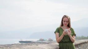 Modniś dziewczyna z plecaka chwytem na mądrze telefonu gadżecie w piasek linii brzegowej Podróżnik używa w żeńskiej ręki wiszącej zbiory