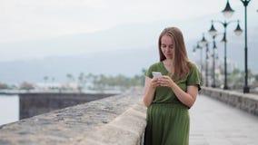 Modniś dziewczyna z plecaka chwytem na mądrze telefonu gadżecie w piasek linii brzegowej Podróżnik używa w żeńskiej ręki wiszącej zdjęcie wideo
