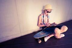 Modniś dziewczyny deskorolkarz słucha muzyka Obraz Royalty Free