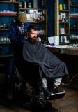 Modniś fryzury pojęcie Modnisia klient dostaje ostrzyżenie Fryzjer męski z cążki arymażu włosy na nape klient barber Fotografia Royalty Free