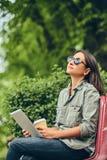 Modniś kobieta w okulary przeciwsłoneczni z kawy i pastylki komputerem Obraz Stock