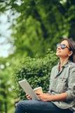 Modniś kobieta w okulary przeciwsłoneczni z kawy i pastylki komputerem Fotografia Stock