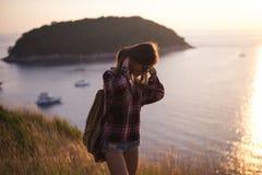 Modniś kobiety elegancki podróżnik patrzeje na oceanie lub morzu przy zmierzchem Obrazy Royalty Free