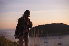 Modniś kobiety elegancki podróżnik patrzeje na oceanie lub morzu przy zmierzchem Obraz Stock