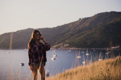Modniś kobiety elegancki podróżnik patrzeje na oceanie lub morzu przy zmierzchem Fotografia Royalty Free