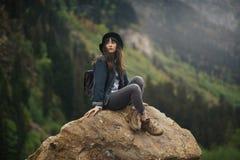 Modniś młoda dziewczyna z plecakiem cieszy się zmierzch na szczytowej górze Turystyczny podróżnik na tło doliny krajobrazu widoku zdjęcie stock