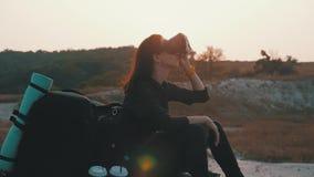 Modniś młoda dziewczyna z plecakiem na wierzchołku skała używa rzeczywistość wirtualna szkła w zmierzchu Aktywny nowożytny zbiory