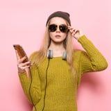 Modniś młoda kobieta używa telefon komórkowego i wybierający muzykę słuchać na hełmofonach Zdjęcie Stock