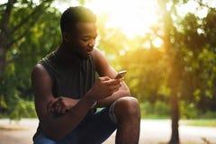 Modniś, młody człowiek używa smartphone Amerykanin Afrykańskiego Pochodzenia nastolatek trzyma mobilnego smartphone przy zmierzch zdjęcia stock