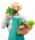 Modniś ogrodniczki odzieży fartuch niesie warzywa Mężczyzna warzyw brodaty przedstawia biały tło odizolowywający Średniorolna sło obrazy royalty free