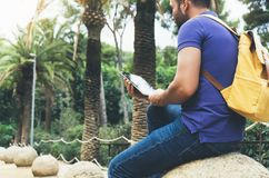Modniś osoby mienie w ręki cyfrowej pastylce z pustym ekranem, mężczyzna fotografia na komputerze na tło natury parka palmy ziemi zdjęcia stock